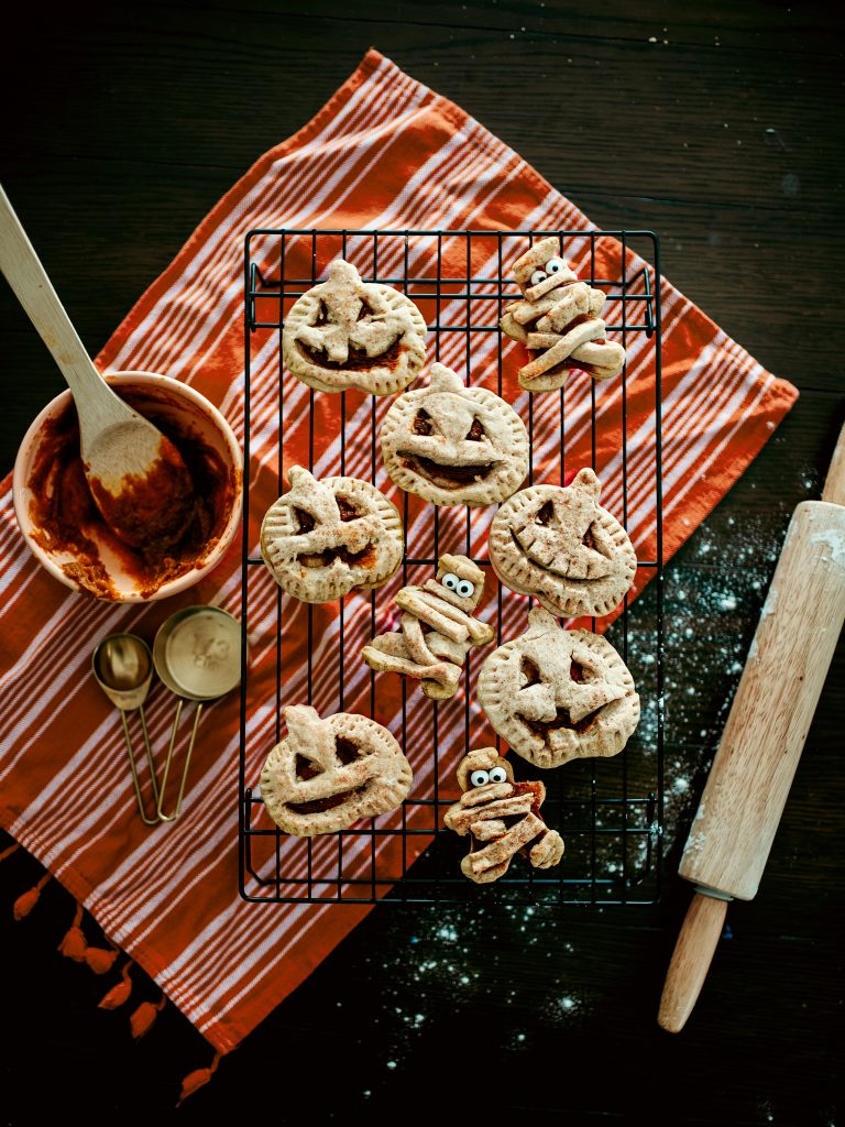 Baking adorable pumpkin hand-pies in the shape of mummies and jack-o-lanterns