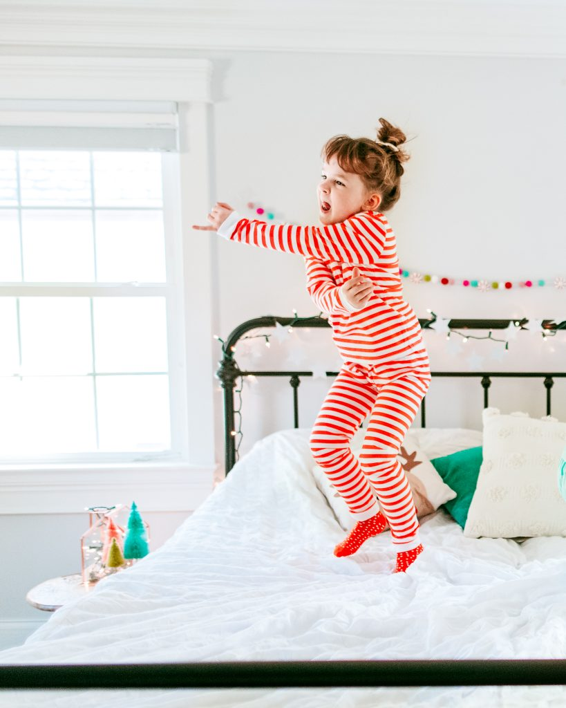 Little girl jumping in candy cane jammies
