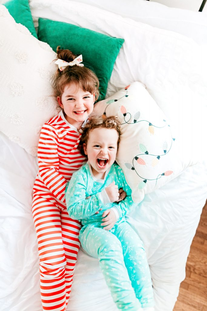 Brother and sister laughing in holiday jammies