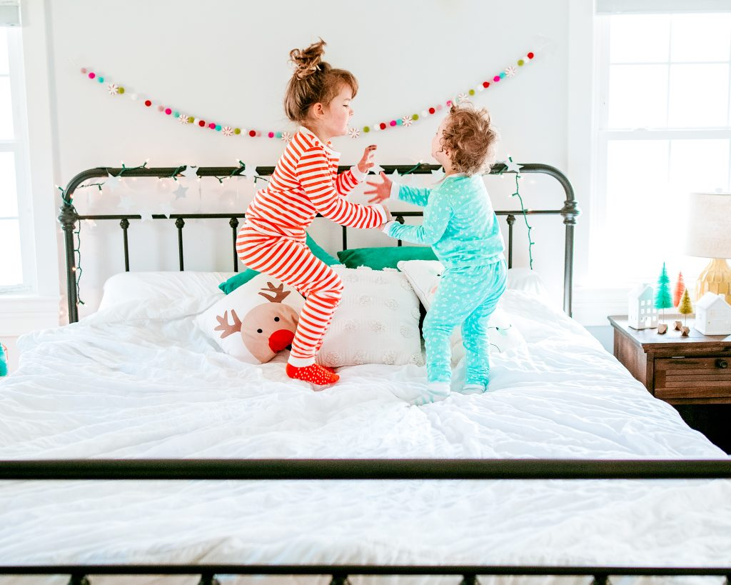 Brother and Sister jumping on festive bed!