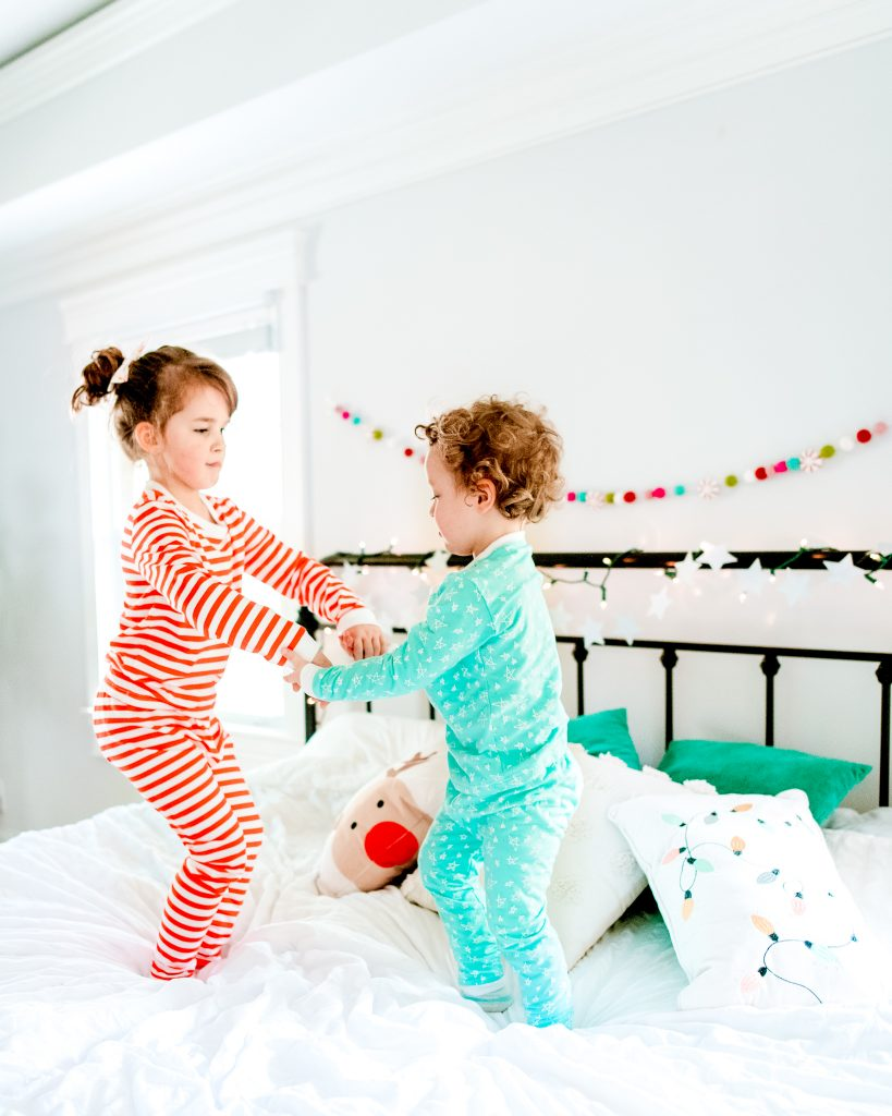 Siblings Dancing on Bed at Christmastime