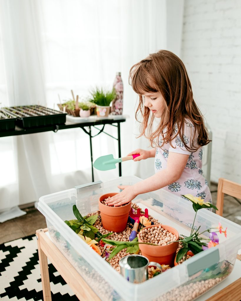 Indoor garden Sensory bin filled with pots, flowers, shovels, and watering cans