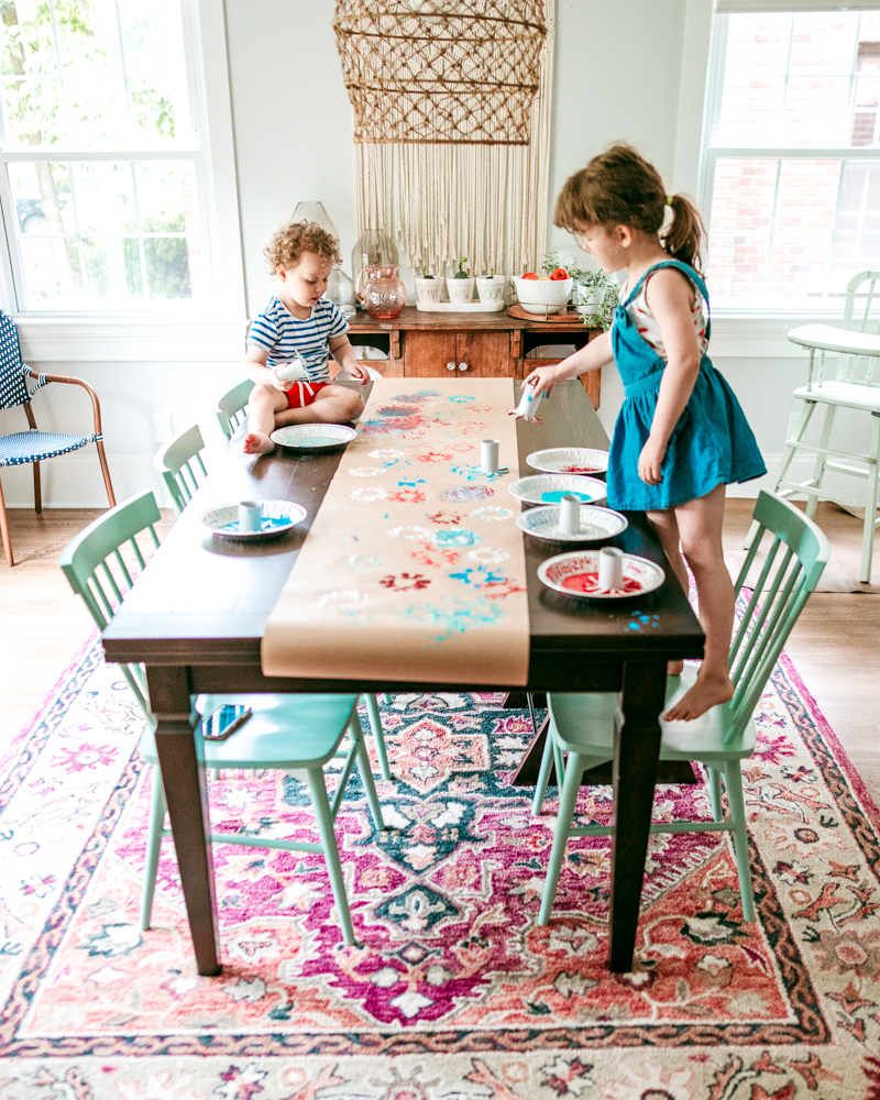 Make a 4th of July table runner using paint and paper roll firework stamps. A fun July art activity for kids!