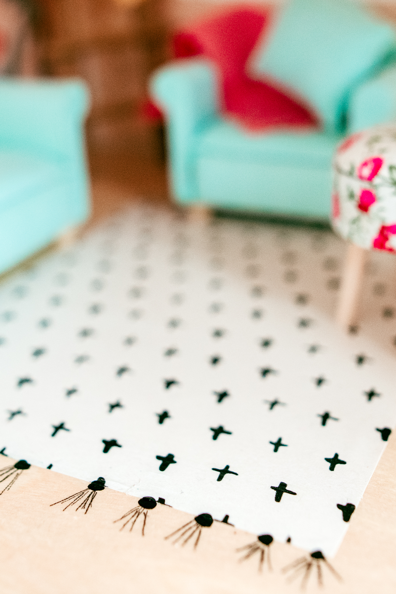 DIY a dollhouse rug using wrapping paper, mod-podge, and a sharpie! See more dollhouse renovation tips