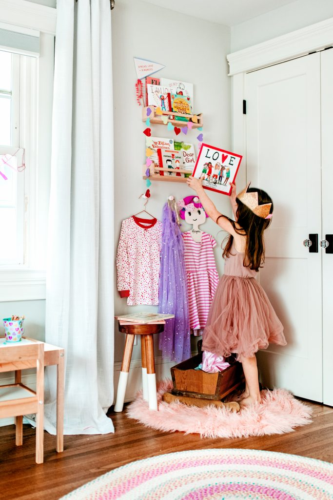 A whimsical book corner for a little girl's room filled with Valentine's Day books for kids