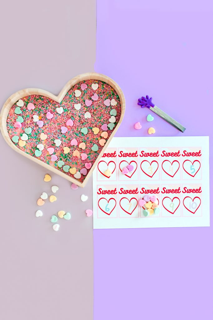Sensory bin for hands on Valentine math activity. Preschool and Kindergarten. Conversation hearts for counting, grouping, and addition. Free printable.