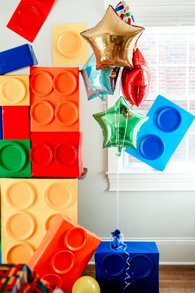 DIY decorations for a lego birthday party! Use boxes, poster board, and paper plates to create giant legos!